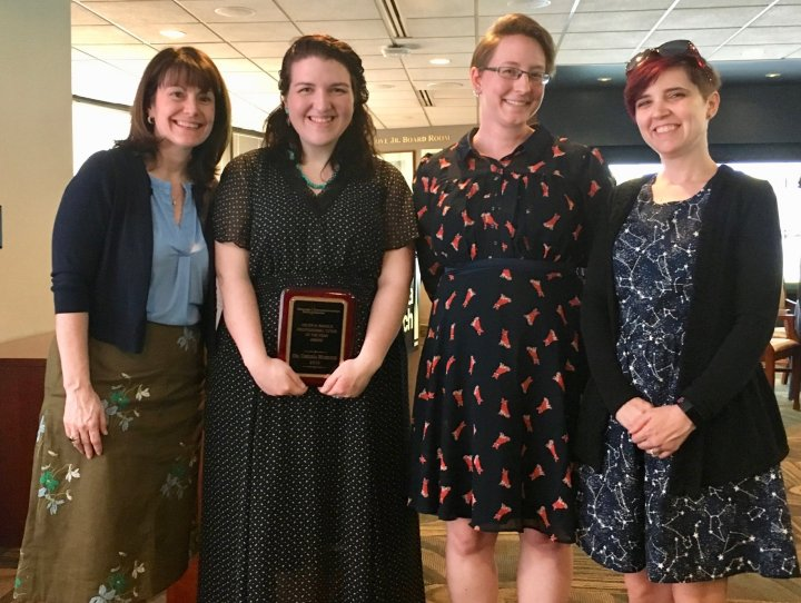 Chelsea, in a long black dress and holding an award plaque, stands with four other women, including Karen Head (in a blue button-up shirt and gold skirt), Leah Misemer (in a fox-patterned dress), and Brandy Blake (in a constellation-patterned dress).